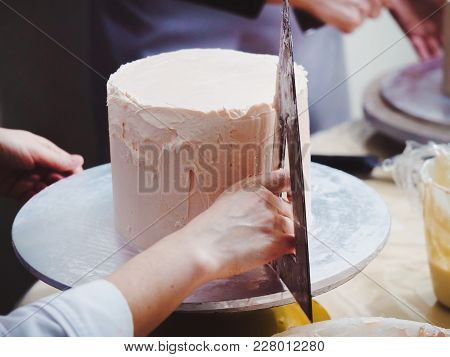 Close Up Of Woman In Bakery Decorating Cake With Icing. Woman's Hand Levels Cream On Mousse, Decorat