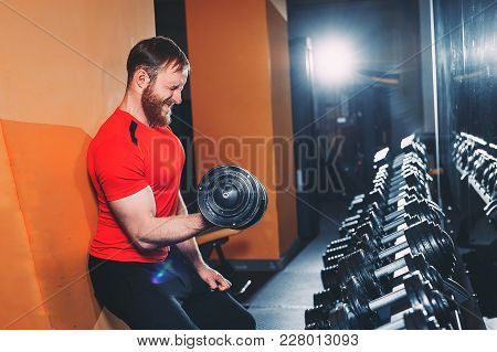 The Athlete Is Engaged In Dumbbells In The Gym