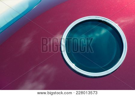 Round Window Similar To A Porthole In A Crimson Car. Car Window Close-up. Design Of The Car. Details
