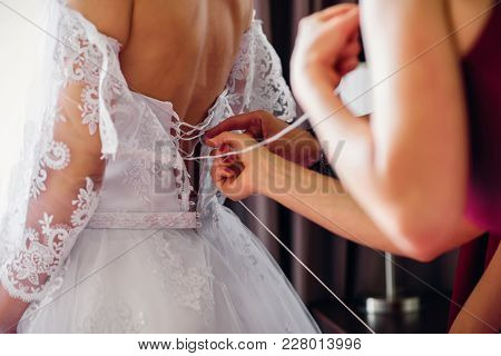Bridesmaids Lace Up Wedding White Dress On The Bride's Back On The Wedding Day