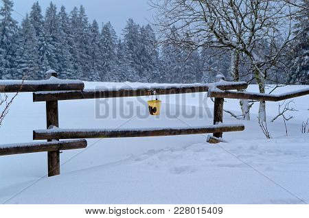 Scenic View Of The Winter Landscape And An Yellow Bucket Hanging On The Railing