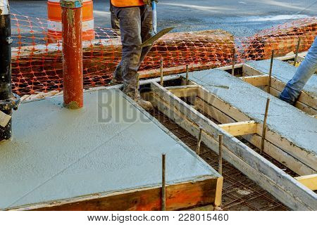 Construction Worker Leveling Concrete Pavement. Masonry Construction Workers Smooth Freshly Poured C