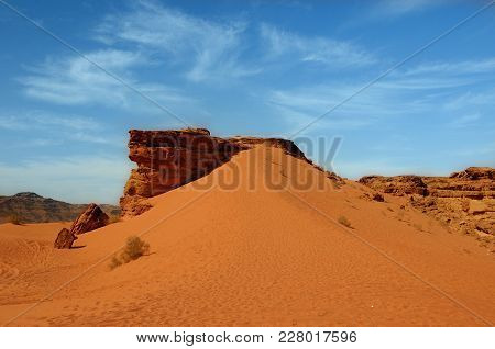 Red Color Desert Cliff With A Sandy Slope And Blue Cloudy Sky In A Background, Wadi Rum, Jordan