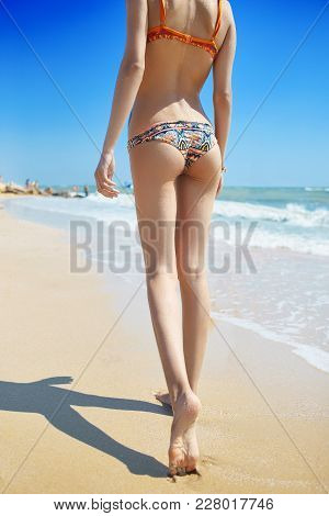 Beautiful Sexual Young Woman Walks On The Beach Against The Sea And Sky. Happy Woman Enjoys Summer V