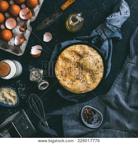 Scrambled Eggs Or Omelette In Cast-iron Frying Pan And Kitchen Accessories Top View. Eggs, Shell, Mi