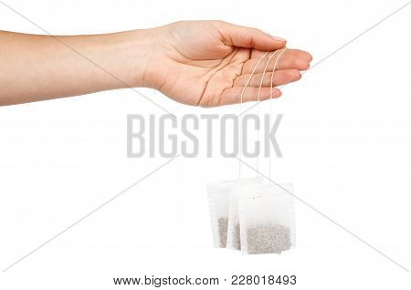 Tea In Paper Bag In Hand. Isolated On White Background. Herbal Teabag.