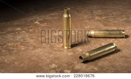 Three Ar-15 Cartridges That Have Been Shot On Sitting On A Beige Floor