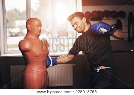 A Man Is Doing Sports In The Gym. He Leads A Healthy Lifestyle. A Man Is Boxing A Mannequin. Body Op