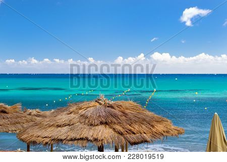 Thatched Umbrellas On The Beach Cafe On The Seafront. Livadi Beach In Sea Bay Of Resort Village Bali