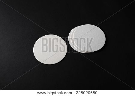 Blank White Beer Coasters On Black Paper Background. Responsive Design Mockup.