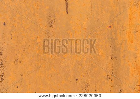 Textured Background Of A Faded Yellow Paint With Rusted Cracks On Rusted Metal. Grunge Texture Of An