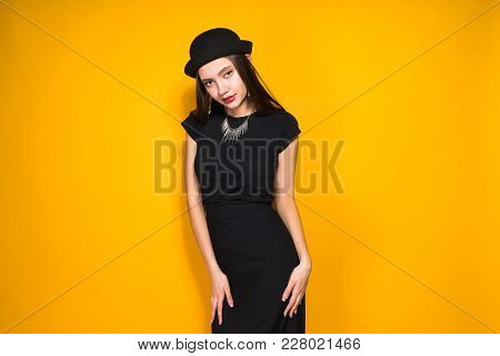 Beautiful Attractive Model Girl In Fashionable Black Hat And Black Dress Posing On Yellow Background