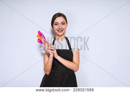Beautiful Young Girl Cook In Black Apron Holding Cooking Tools