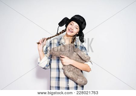 Happy Beautiful Russian Woman In A Cap With Ear-flaps Holds Warm Winter Felt Boots