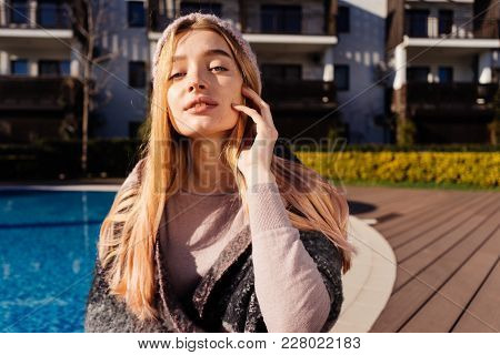Beautiful Attractive Girl With Light Code And Blond Hair Posing By The Pool In The Sun, Wearing A Ha