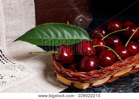 Fresh Organic Cherry And Big Green Leaf In Yellow Wooden Basket On Dark Marble Background..