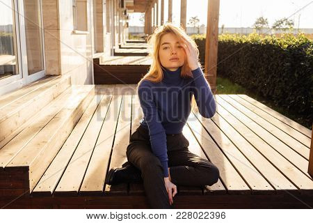 Attractive Young Blond Model Girl In Stylish Blue Sweater Sits Outdoors In The Sun