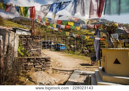 The Mountain Village In Nepal Located On Cascades And Decorated With Traditional Nepal Flags.