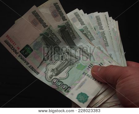 Banknotes In Denominations Of One Thousand Rubles In A Person's Hand. The Money Is Stacked In The Fo
