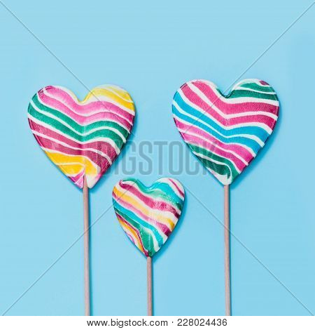 Three Lollipops Rainbow Candy As Heart On Blue. Funny Family Concept. Top View. Square Image.