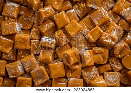 Toffee Candy Brown Background. Caramel Cubes Close Up
