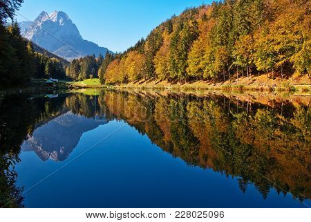 Beautiful Mountain Lake With Rock And Colorful Forest In The Background