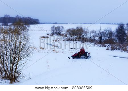 The Man On The Snowmobile Across The Field