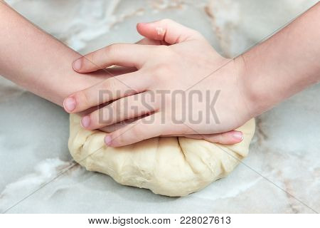 Children Hands Knead The Dough On The Table, Closeup