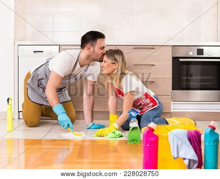 Young Couple Cleaning House Together And Having Tender Moments