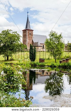 The Church Of Sint-pieters-voeren Mirroring On The Water Surface Of One Of The Ponds Of The Commande