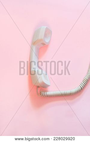 Top View Of White Telephone Handset, Receiver And Cord Isolated On Pink Background.