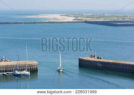 Sailing Ship Leaving Harbor Of Helgoland, German Island In The Northsea. At The Horizon The Smaller