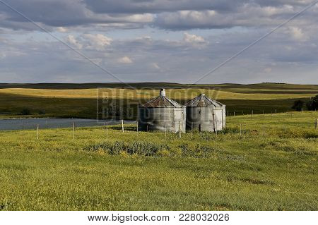 Several Abandoned Round Grain Bins Stand Isolated In The Vast Hilly And Treeless Prairie