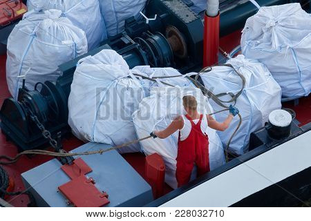 Worker In A Red Suit On A Cargo Ship.