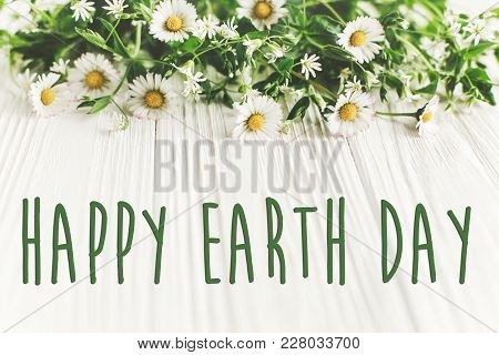 Happy Earth Day Text Sign On Beautiful Daisy Flowers On Rustic White Wooden Background Top View. Gre