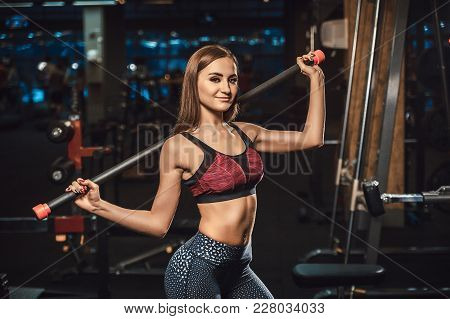 Beautiful Young Fitness Girl Posing With Sport Equipment In Dark Gym Looking At Camera. Posing With