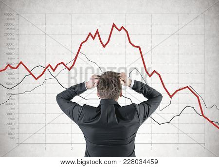 Portrait Of A Blond Businessman Wearing A Suit And Pulling Out His Hair In Panic. A Rear View. Graph