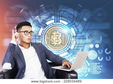Asian Businessman In A Suit And Glasses Is Sitting With His Laptop In An Armchair. A Shining Bitcoin