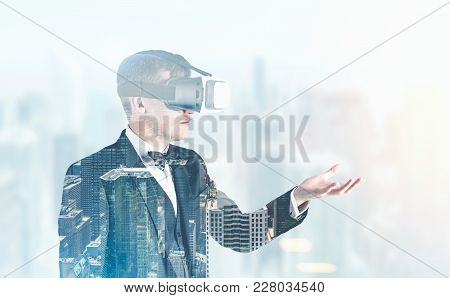 Side View Of A Handsome Fair Hair Businessman Wearing Vr Glasses, A Bow Tie And A Suit. He Is Standi