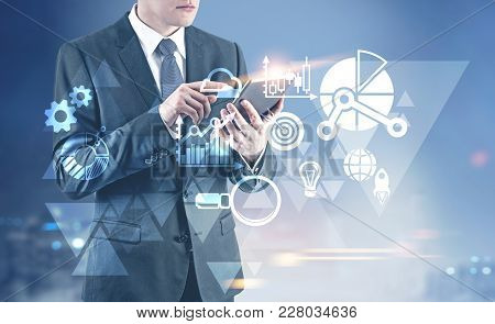 Unrecognizable Young Businessman Wearing A Dark Suit With A Tie And Working With A Digital Tablet. I