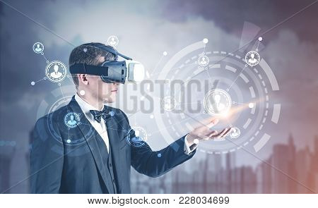 Side View Of A Fair Hair Businessman Wearing Vr Glasses, A Bow Tie And A Suit Showing A Network Hud