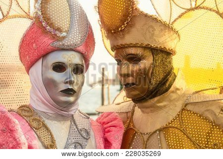 A Pair Of Costumed Revelers Of The Carnival Of Venice In A Silver, Pink, And Gold Costumes.