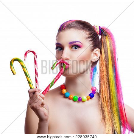 Portrait Of A Young Girl With Colorful Creative Makeup And Colored Strands Of Hair. The Woman Holds