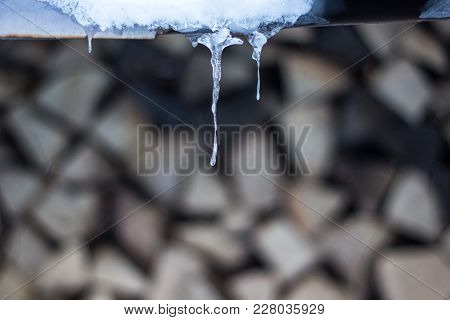 Icicles And Firewood In The Background Winter