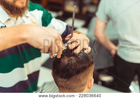 Barber Using Scissors And Comb. Man Haircut In The Barbershop.