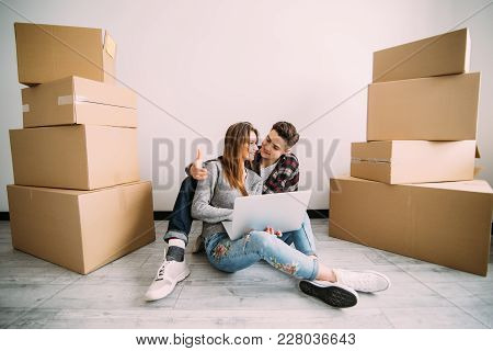 Young Couple Moving In A New Home. Man And Woman With Notebook Laptop Computer And Boxes In Empty Ro