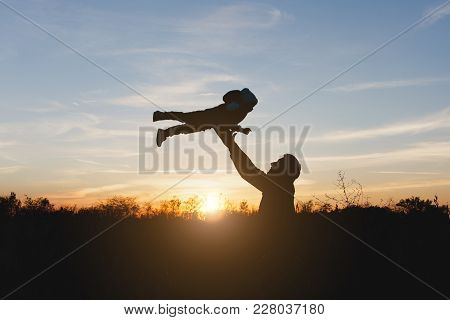 Silhouette Of Man High Toss Up Little Cute Child Baby Boy On Nature, Sunset Horizon Background. Fath