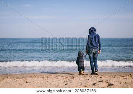 Young Woman Standing At Sea Beach Background Holding Hand Little Cute Child Baby Boy, Looking On Hor