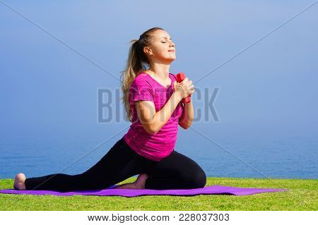 Young Woman On Grass With Dumbbells In Hands On The Background Of The Sea. Fitness Girl Doing Exerci