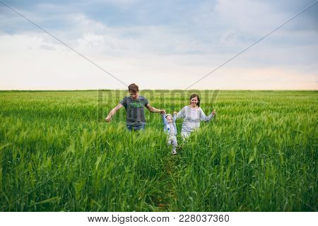 Joyful Man, Woman Walk On Green Field Background, Rest, Have Fun, Play, Run With Little Cute Child B